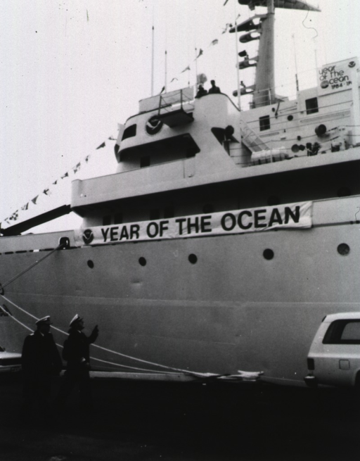 <p>Surgeon General Koop and another man in uniform walk on the docks next to a NOAA vessel on which is the banner, Year Of The Ocean.</p>