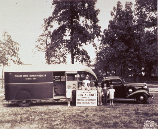 <p>Children and a dentist are standing in front of a mobile dental unit.</p>