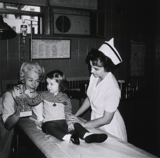 <p>Auxillary volunteer and child in emergency room.</p>