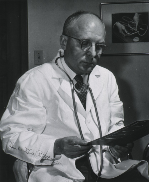 <p>Half length, right pose, hands showing, white coat, stethescope around neck.</p>