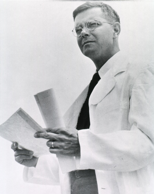 <p>Three quarter length, standing, full face, wearing white coat, body to left, holding papers.</p>