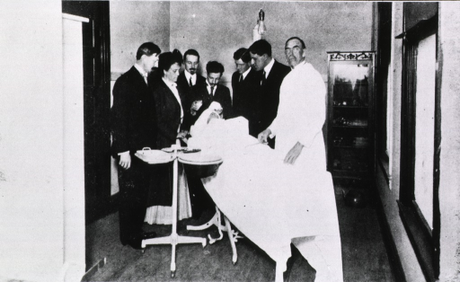<p>One female and five male students grouped around a patient during advanced surgical class.  The surgeon looks at the camera.</p>