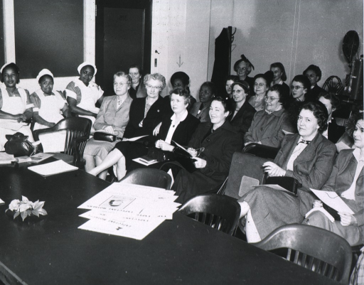 <p>View of women meeting to discuss the Midwives Institute.  African American women in uniforms are sitting against the wall by the door.</p>