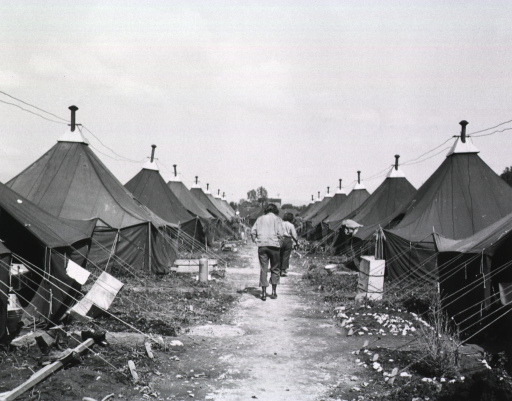 <p>Two female nurses walk down a path that separates two rows of tents.</p>