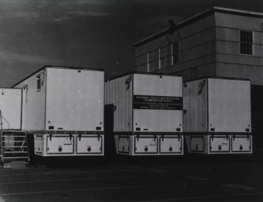 <p>Exterior view showing the back ends of three trailers in a parking lot.</p>