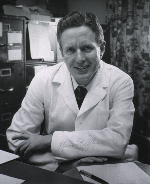 <p>1/2 length, full face, seated at desk wearing white coat.</p>