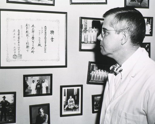 <p>Half length, left profile, standing beside wall of portraits and diploma, written in Japanese.</p>