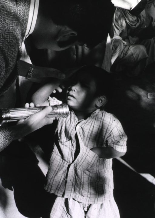 <p>A man using a flashlight is examining the eyes of a young boy.</p>