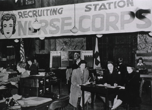 <p>Interior view: large room with several tables and boxes of files; several women sit at tables; a large recruitment banner spans the room, and a poster display explaining the Nurse Corps is in the background.</p>