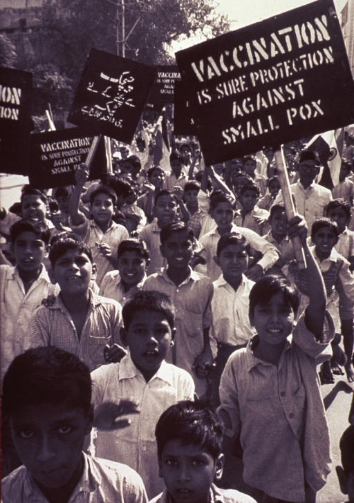 <p>A large group of schoolboys carrying signs urging vaccination against smallpox.</p>