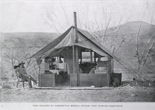 <p>A man is sitting in a chair to the left of a large tent that serves as his living quarters. The tent has a wood floor, partial wood siding, and is outfitted with a stove, a desk, a bed, chairs, and a large mirror.</p>