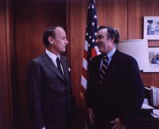 <p>Donald S. Fredrickson, director of the National Institutes of Health (NIH), is standing with his hand in his pocket facing Joseph Califano, secretary of the Dept. of Health, Education, and Welfare.  There is a U.S. flag by Secretary Califano's right shoulder.  Behind him is a desk, a lamp, and pictures on the wall.</p>
