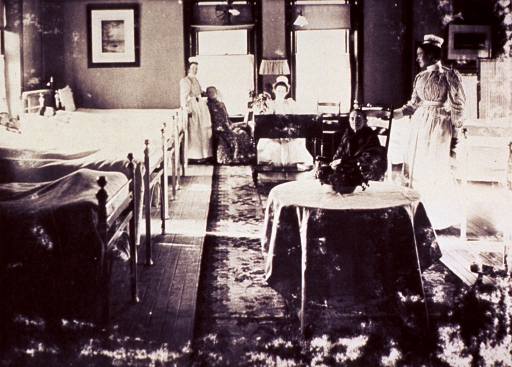 <p>Interior view of room; beds are along walls on the left and right; nurses are standing with patients sitting in the center aisle.</p>