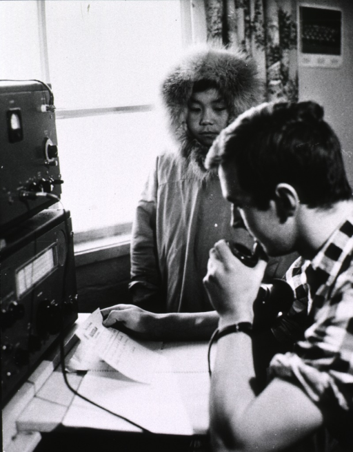 <p>Interior view: a young Eskimo is standing next to a radio operator as help is summoned.</p>