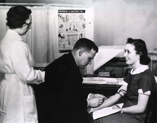<p>Showing a doctor taking a blood sample from a young woman.  A nurse stands behind the doctor.</p>