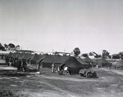 <p>Servicemen stand in a line next to a group of tents.</p>
