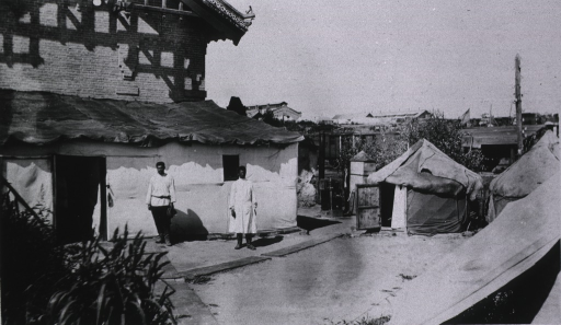 <p>Two medical personnel stand outside the Red Cross Hospital.  The round tent structures are used as nurses quarters.</p>