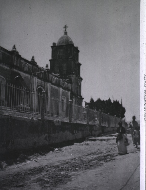<p>Three people walk beside the Church.</p>