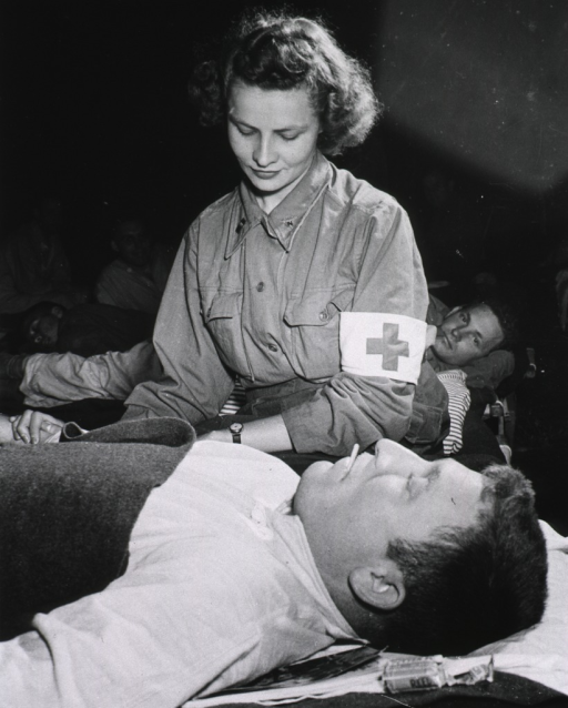 <p>A nurse, Lt. Elizabeth Babarsik, takes the pulse of a soldier, Pvt. John L. Bennett, lying on a cot; other patients are in the background.</p>