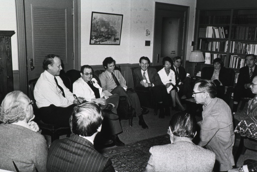 <p>Dr. Donald S. Fredrickson, director of the National Institutes of Health, is sitting in a circle with 13 other people.  Dr. Fredrickson is holding his eye glasses.  There is a built-in bookcase perpendicular to the door with glass.  A louvered door is behind Dr. Fredrickson.  Between the two doors is a painting.  The group is discussing a replacement for the deputy director (science) position due to the retirement of Hans Stetten.</p>
