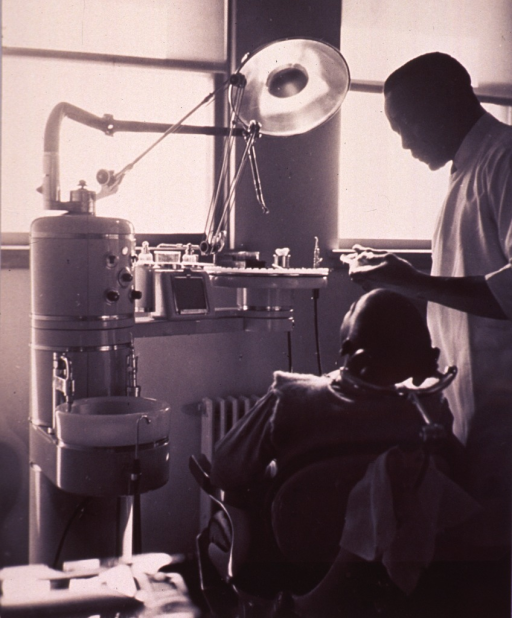 <p>Interior view of a dental office with an African American patient sitting in the dental chair and a dentist standing next to him.</p>