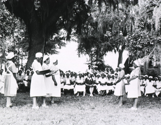 <p>African American nurse midwives are standing before a large group that is seated under the trees.  Two of the women standing are holding large books.</p>