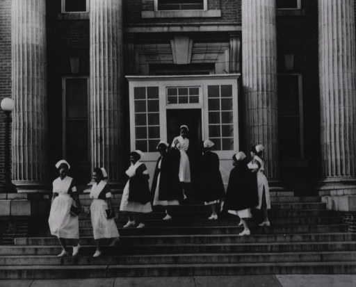 <p>Close-up of the entrance to the Freedmen's Hospital; some African American nurses are going up and others are going down the exterior steps.</p>