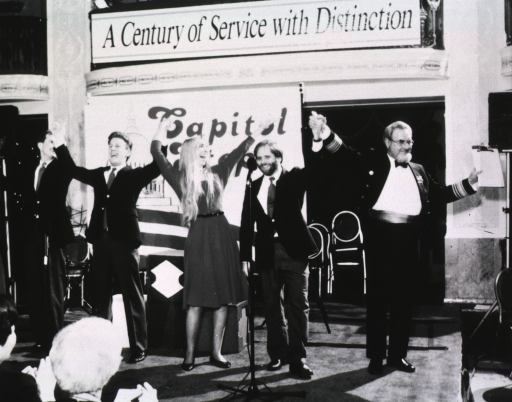 <p>C. Everett Koop and the entertainers, The Capitol Steps, stand hand in hand across a stage during the gala to inaugurate the centennial year of the USPHS Commissioned Corps.</p>