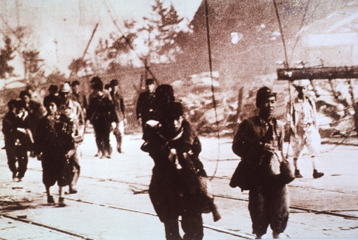 <p>Survivors and rescue workers on the main road from the Urakami Valley.  The child being carried, in the foreground, had his face burned black by the flash.</p>