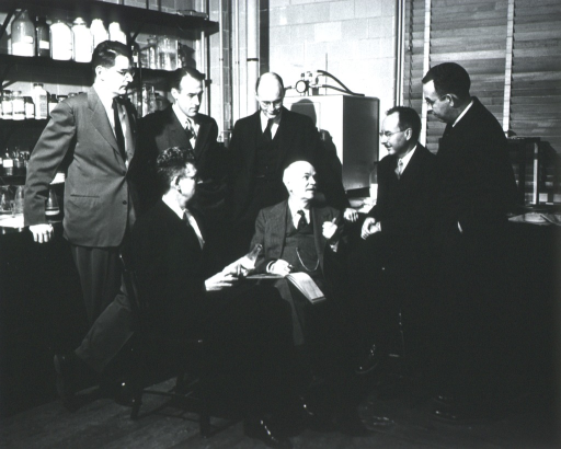 <p>Full length, seated with six men around him.</p>