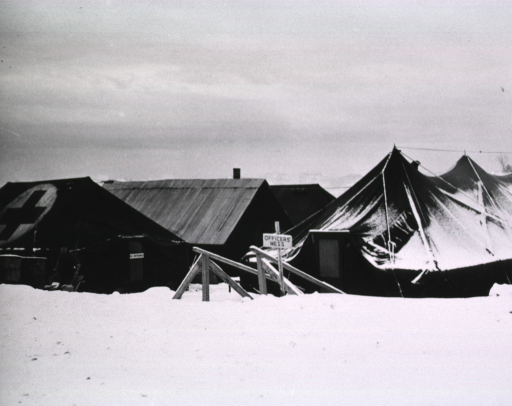 <p>A serviceman is seen carrying boxes outside of a tent.  The ground is covered with snow.  In front of another tent is a sign:  &quot;Officers' Mess&quot;.</p>