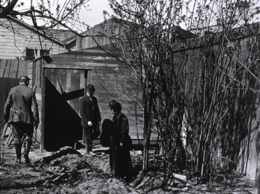 <p>A health inspector dressed in plain clothes (in background, walking forward) threatens the destruction of an illicit backyard stable unless concrete is installed; the Public Health and Marine Hospital Service District Commander (facing back) approaches to give further explanation to the woman (standing in ditch) guilty of erecting it.</p>