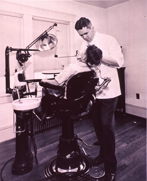 <p>Interior view of a dental office; a dentist is working on a patient's teeth.</p>