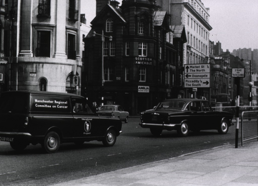 <p>Exterior view: an automobile on a city street; the vehicle is identified as belonging to the Educational Project of the Manchester Regional Committee on Cancer.</p>