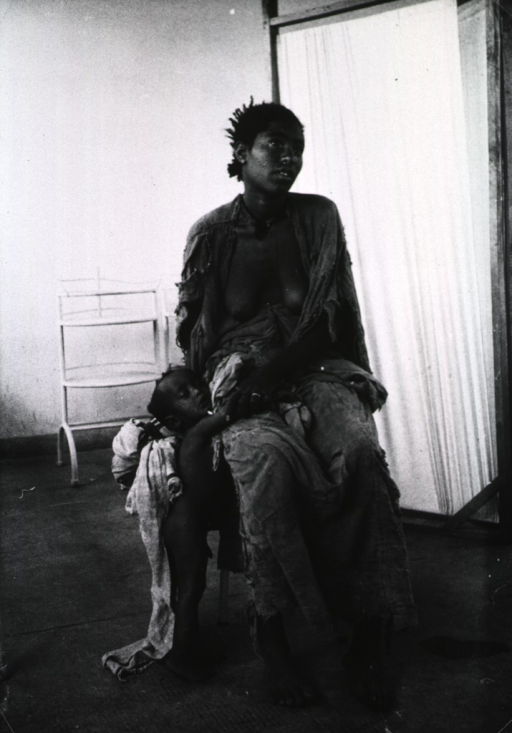 <p>A woman wearing ragged clothing is sitting in a chair, a young boy is standing next to her; they are in the unfamiliar surroundings of a modern health care center.</p>