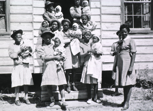 <p>Clinic in church, Cainhoy, South Carolina, showing Eugenia Broughton and several African American mothers with their babies.</p>
