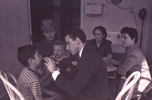 <p>Interior view of an office; a dentist is examining a boy's teeth as three women and two children observe.</p>