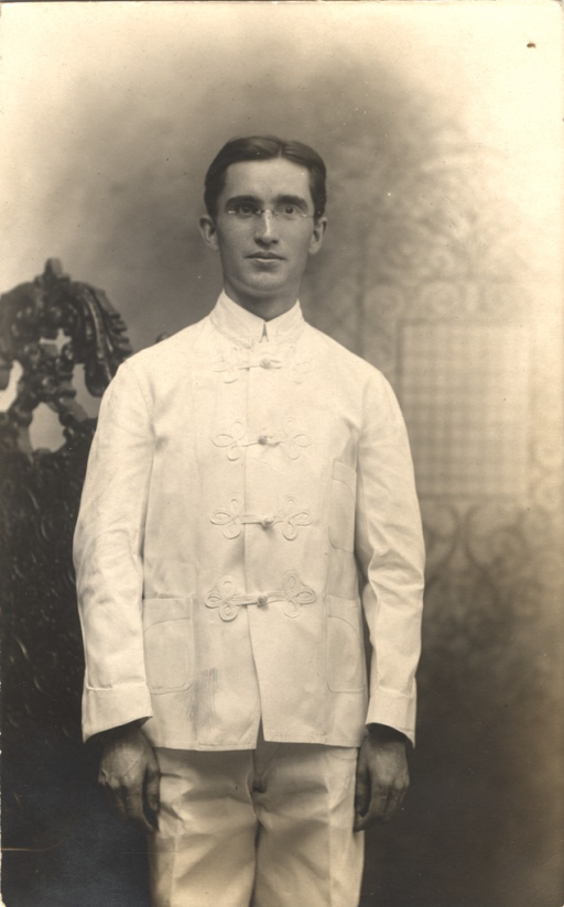 <p>Postcard featuring a black and white photograph of a man in a white uniform. He is possibly a graduate of the National Training School for Missionaries in Washington, D.C. He is wearing glasses.</p>
