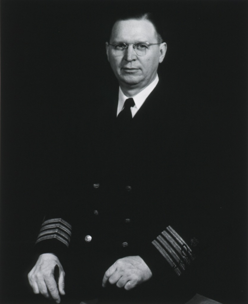 <p>Three-quarter length, seated, left pose, full face; wearing naval uniform and glasses.</p>