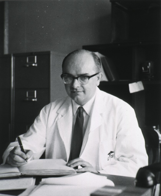 <p>Half length, full face, seated at desk, wearing white coat, writing in notebook.</p>