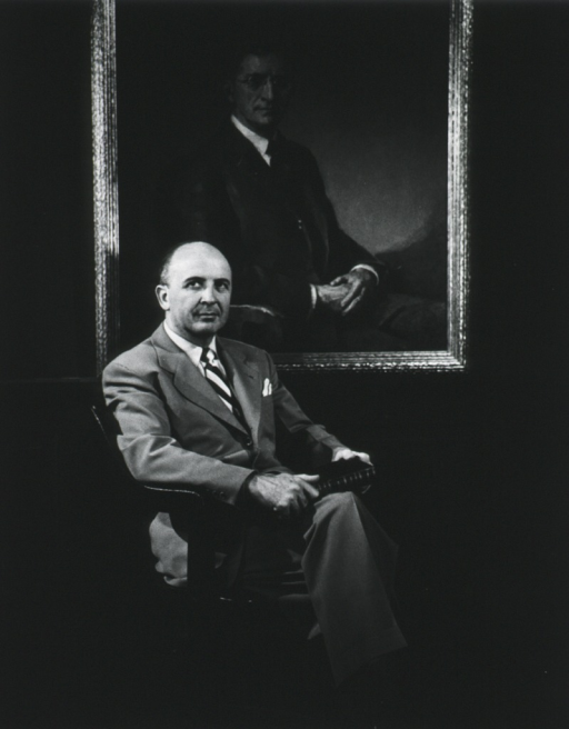 <p>Three quarter length, full face, looking up and to the left, seated under portrait of Goldberger.</p>