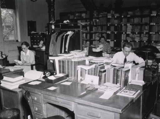 <p>Interior view:  Staff members are seated at their desks.  On the desk in the foreground are reference materials, a telephone, and an ashtray.  Material is on book shelves and a rack with coats and hats are in the background.</p>