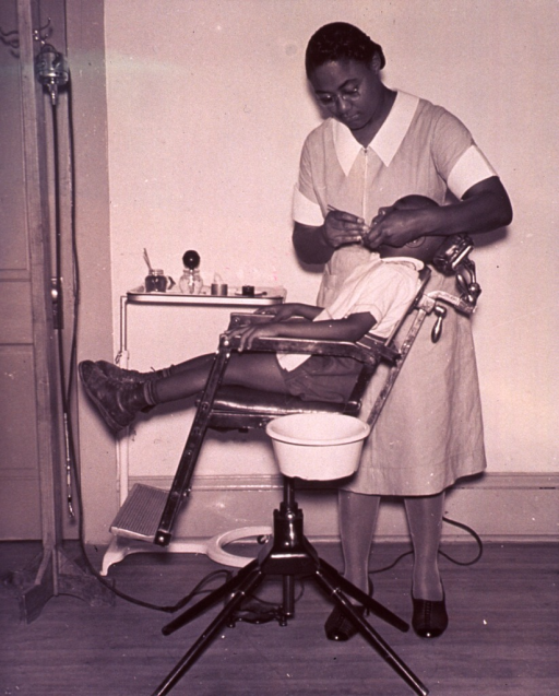 <p>An African American dentist is working on a patient's teeth in a sparsely furnished office.</p>