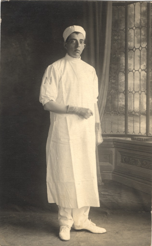 <p>Postcard featuring a black and white photograph of a man wearing a white uniform and a long white gown to protect his clothing. He is wearing a hat and has gloves on his hands. There is an &quot;N&quot; on the right sleeve of his shirt.</p>