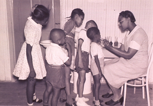 <p>An African American dentist is examining a patient's teeth as several other children observe.</p>