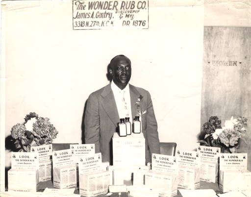<p>A man in a suit poses behind a counter on which sits a display of bottles in boxes with the caption: &quot;Look: The Wonder Rub, a new discovery.&quot;</p>
