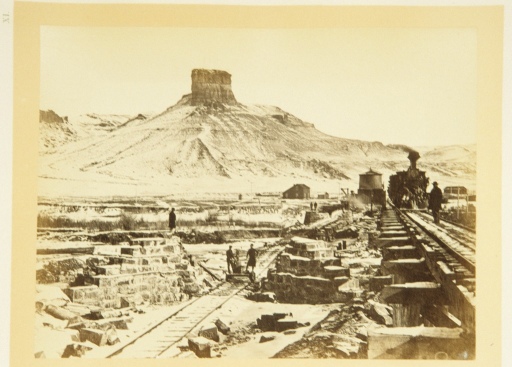 <p>View of rock formations, buildings, and workers on and near a bridge of the Union Pacific Railroad. In the foreground, men stand on the tracks; a train appears on one of the tracks; in the distance rises Citadel Rock.</p>