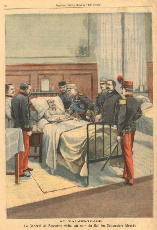<p>The general, in full military regalia, shakes the hand of the wounded solder who lies in a bed in a hospital ward.  Other military figures stand around the bed and watch the meeting.</p>
