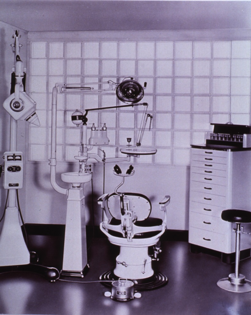 <p>Interior view: chair, dental unit; chair faces a glass bricked wall.</p>