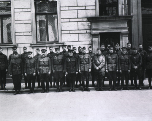 <p>Showing Grissinger with staff; all full face; standing on steps in front of building.</p>